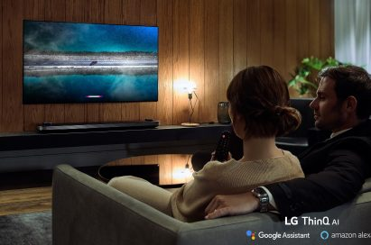 A couple is watching an LG TV supporting Amazon Alexa while the woman holds the remote in one hand