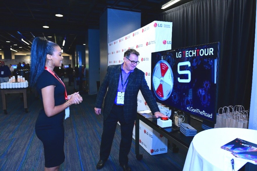 A woman takes an attendee through LG's promotional spin the wheel game.