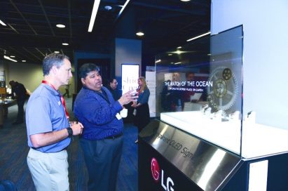 Two attendees discuss about the new Transparent LG OLED display.