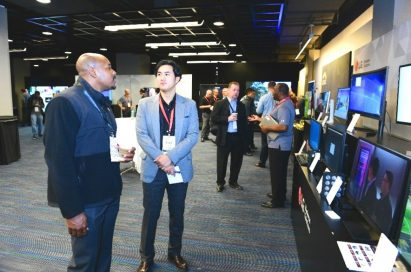 A group of attendees discuss LG's B2B monitor solutions.