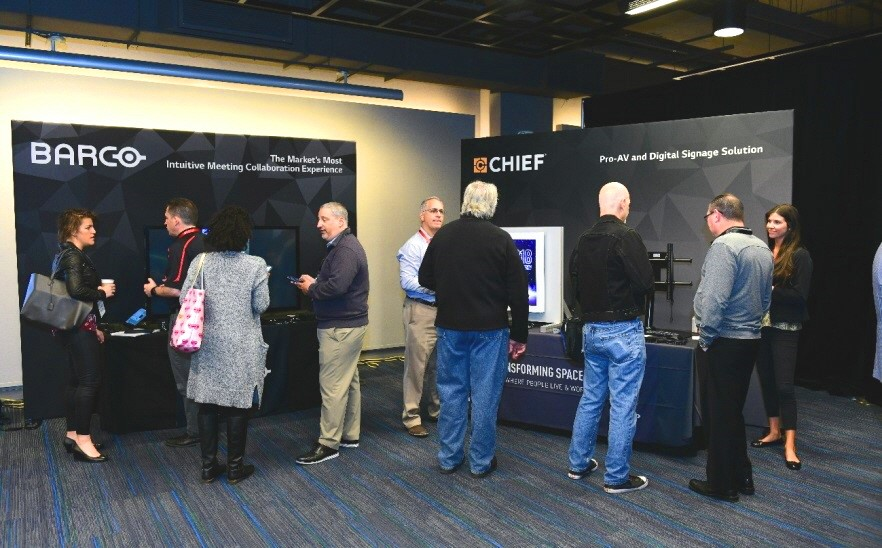 Attendees talk to each other in front of the promotion booths of LG's technology and service partners, Barco and Chief.