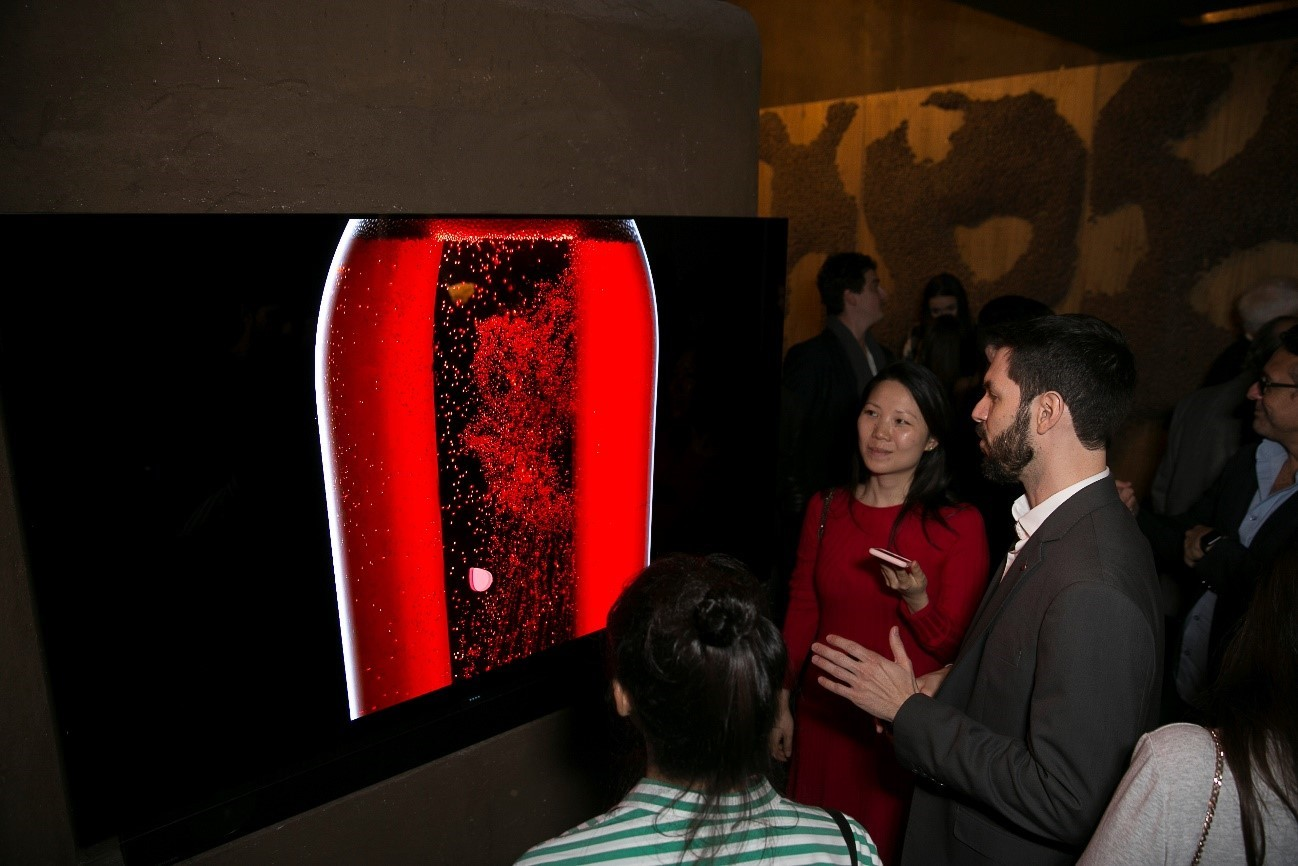 Visitors look at and discuss LG's 77-inch OLED TV inside of LG's Planet Home.