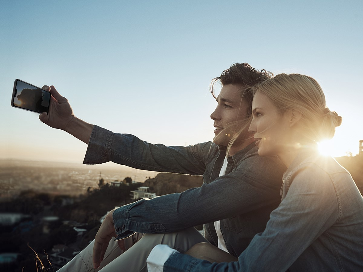 A man holds the LG V50 ThinQ out to take a selfie with a woman with the sunset in the background.