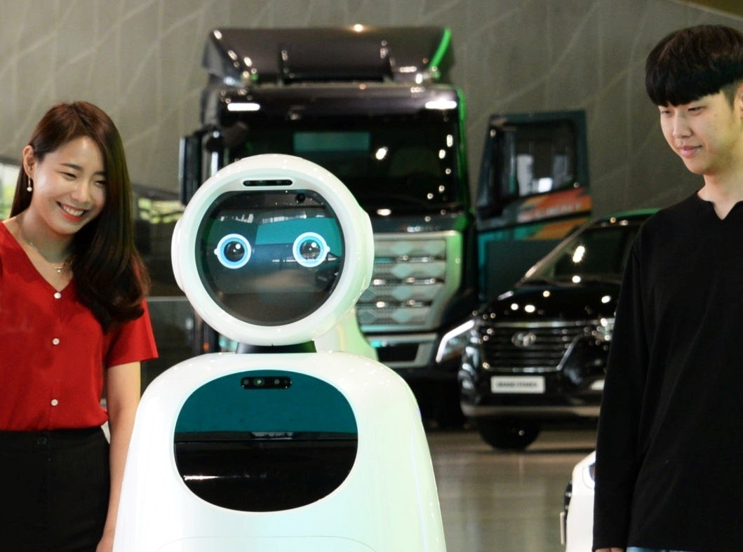 A woman and a man stand next to LG CLOi GuideBot in front of vehicles at Hyundai Motor Studio Goyang.