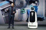 Park Il-Pyung, president and CTO at LG Electronics, stands next to LG CLOi GuideBot on stage to explain LG's ThinQ AI platform.