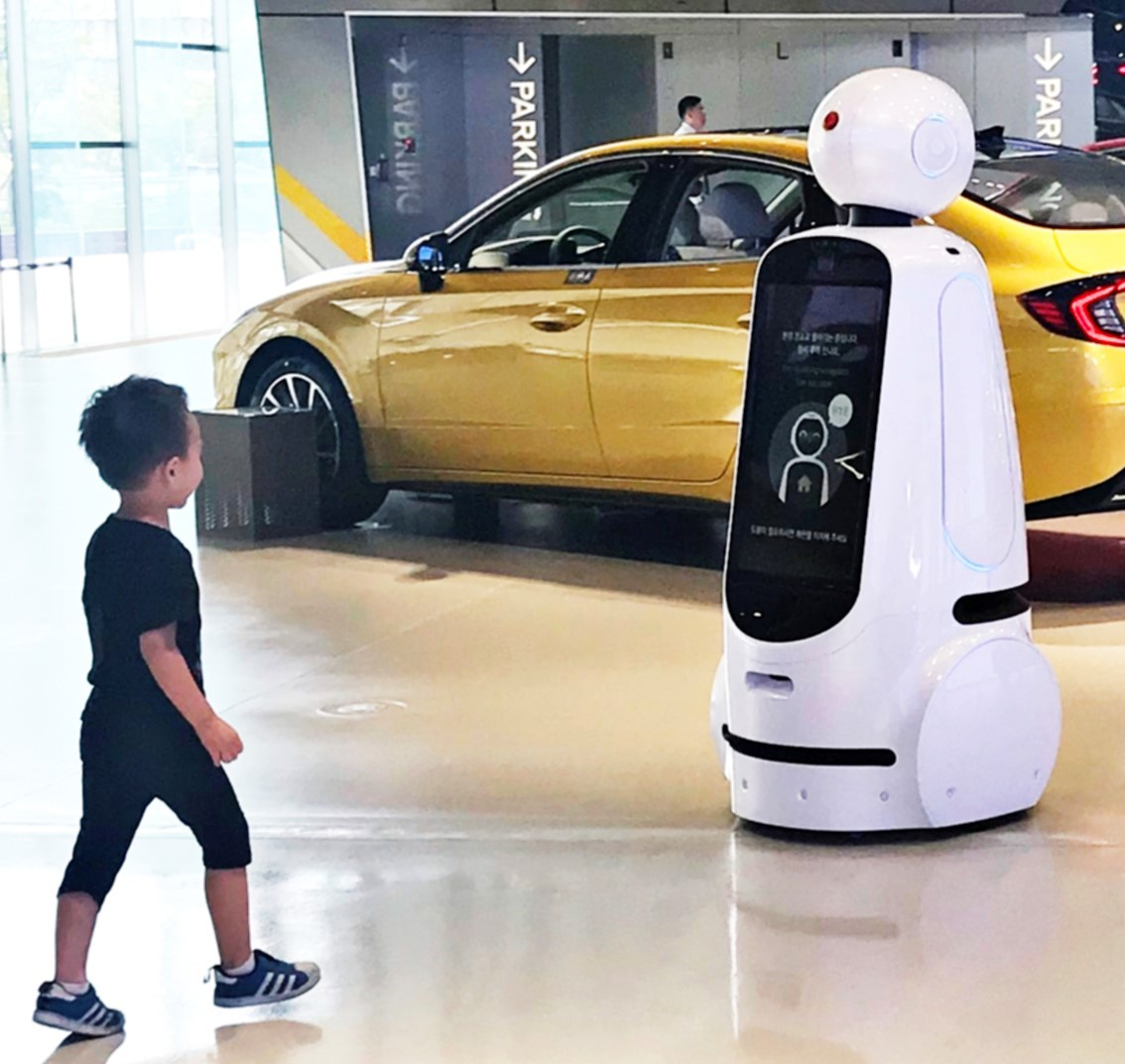 A little boy walks towards LG CLOi GuideBot at the Hyundai Motor Studio Goyang.