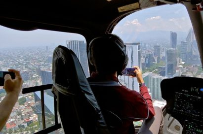 A pilot and a passenger take photos in the helicopter by using LG Q60.