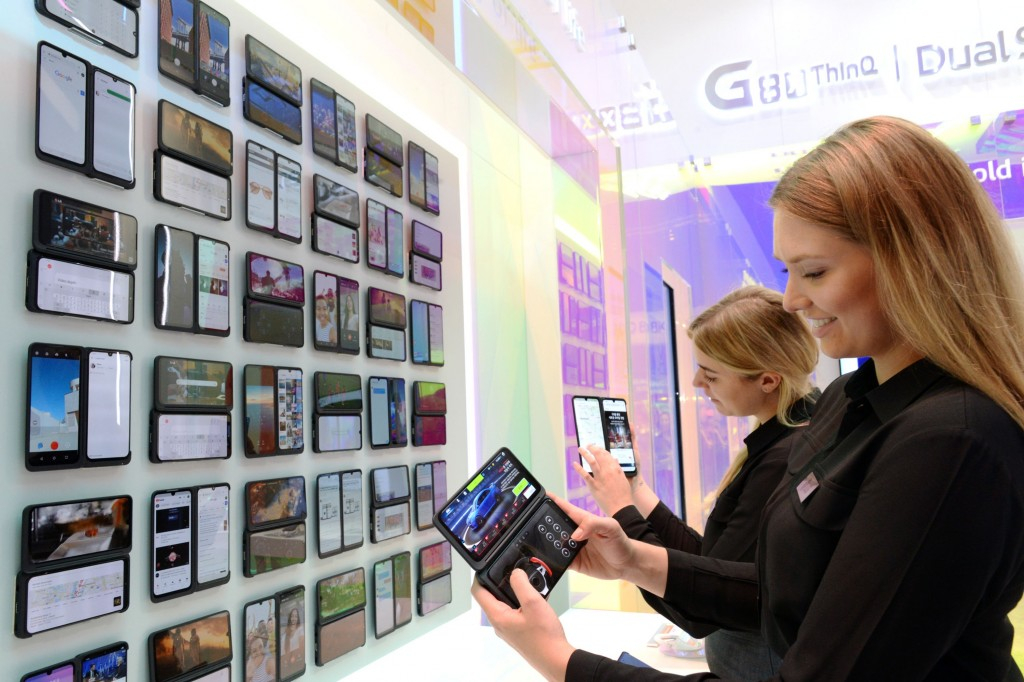 Two female models hold up the LG G8X ThinQ smartphones at LG's IFA booth, which demonstrates all the new features of LG G8X ThinQ.