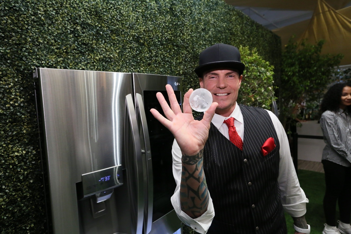 Rapper Vanilla Ice holds up a round LG Craft Ice ball in front of LG InstaView™ Door-in-Door® Refrigerators with Craft Ice.