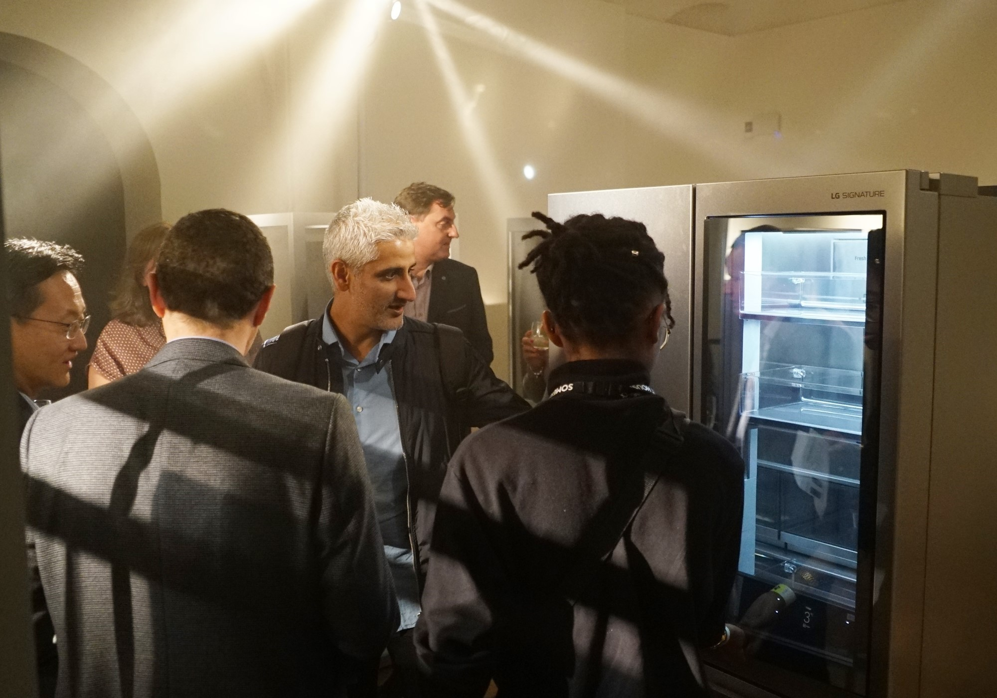 Attendees discuss the LG InstaView Door-in-Door refrigerator at LG SIGNATURE's exhibition space.