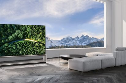 The LG SIGNATURE OLED 8K TV model 88Z9 showing a road in the woods is placed in a modern, spacious room with a spectacular view