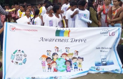 A group photo of participants of the LG Eco Agents of Change campaign holding a banner with an illustration that promotes the importance of young people when it comes to conserving the environment.