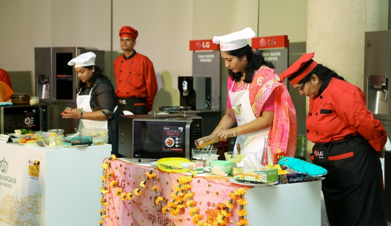 Another view of the participants cooking their Indian food by using LG's microwave ovens at the LG Mallika-E-Kitchen contest.