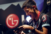 A male gamer plays a video game on the LG G8X ThinQ with Dual Screen, with a large LG logo on the wall in the background.