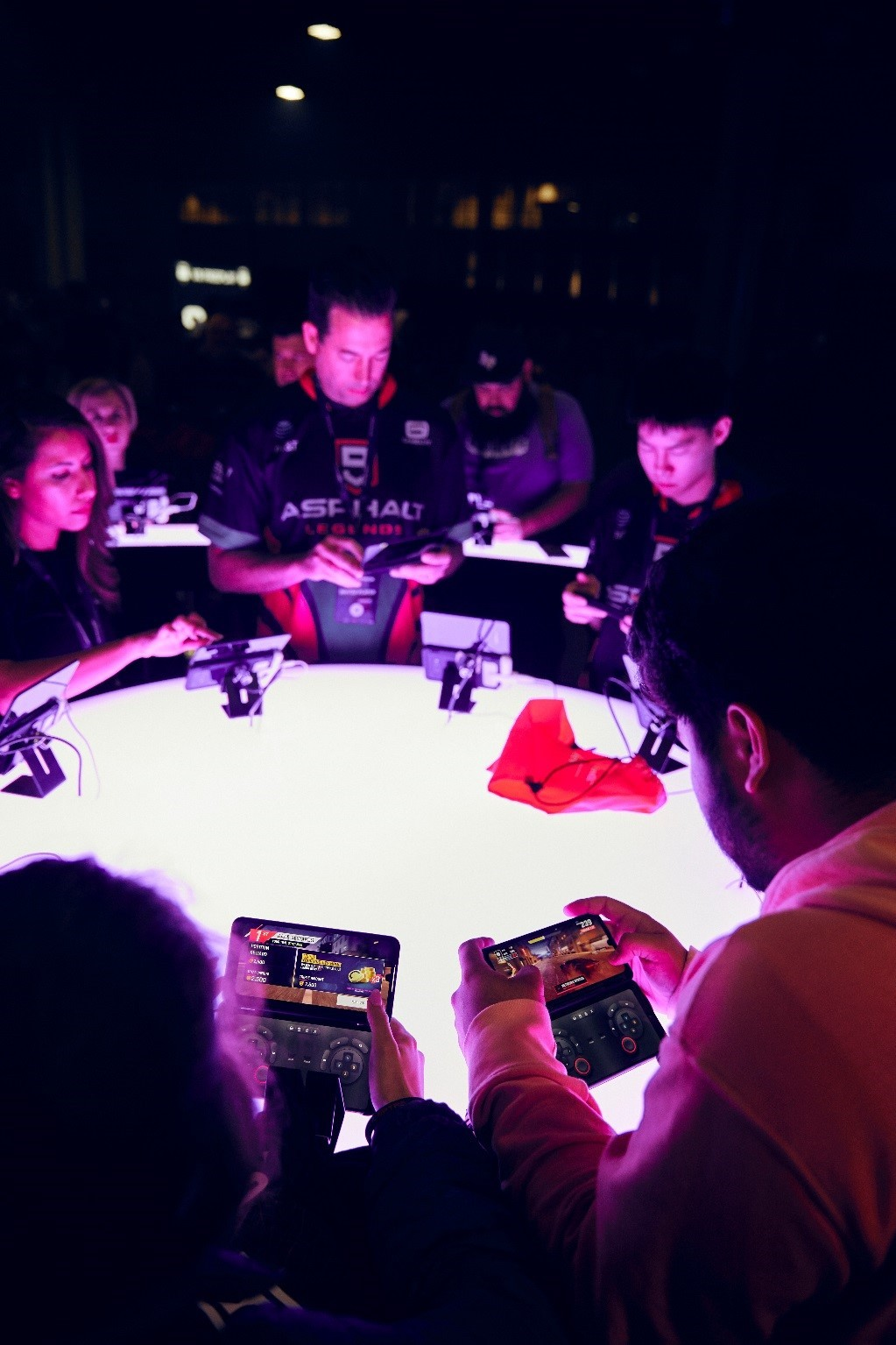 Gamers test out the gameplay on LG G8X ThinQ with Dual Screen around an illuminating round table.