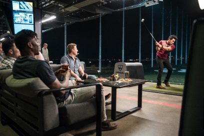 A golfer hits a tee shot as friends watch while sat on the couch at a Topgolf venue.