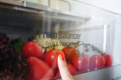A close-up of the LG V+ refrigerator's Fresh Balancer drawer full of tomatoes and lettuce, and a woman pressing her finger up against it.