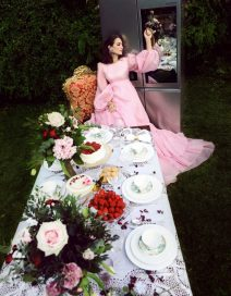A photo recreating the Mad Hatter tea party scene from Alice in Wonderland, with fashion designer Tamara Falcó sitting at the head of a dinner table as she leans back against the LG SIGNATURE Door-in-Door refrigerator and touches the InstaView panel.