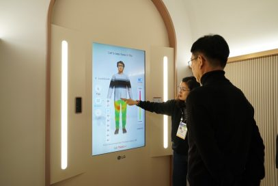 An LG representative takes a visitor through the Style Lab to see how well his clothes fit at the company's CES 2020 LG ThinQ fit Collection booth