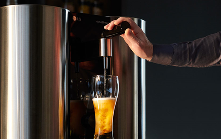 A man holds down the tap of LG HomeBrew to pour the perfect beer