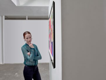 A woman admiring LG's art-inspired Gallery series model GX as it hangs flush on the wall of a gallery thanks to its ultra-thin form factor