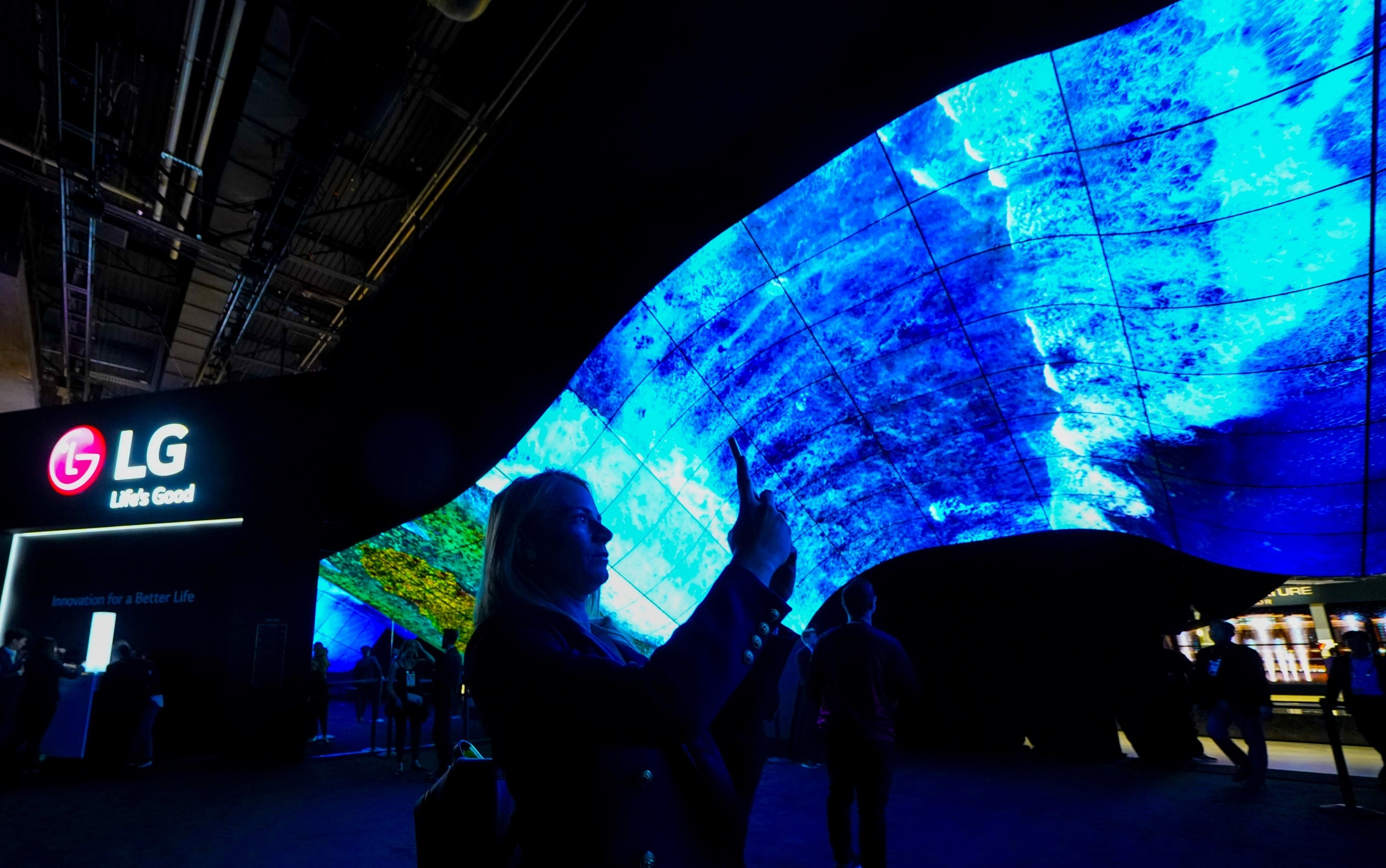 A woman taking a photo of the mesmerizing LG OLED Wave at CES 2020 as it displays vivid blue waves crashing against the coastline