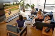 A group of friends gather around LG's 8K OLED TV model ZX TV in the living room to watch a game of baseball