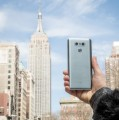 A person holds up the LG G6 to show its rear side with the Empire State Building in the background