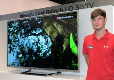 A male attendant stands next to the world's first LG 84-inch 4K 3D TV which is placed on a display stand.