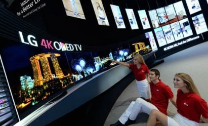 Three models sit down on the floor and look up to the world's first LG 4K curved OLED TV products that are positioned on a display stand.