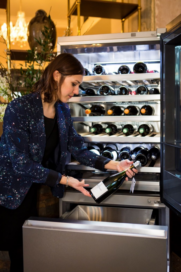 A woman holding a bottle of wine in front of the Wine Cellar