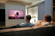 A man and a woman enjoying the state-of-the-art picture quality that comes with LG OLED TV GX on their cozy living room sofa