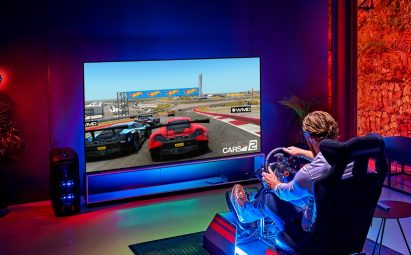 A man enjoys an immersive gaming experience while playing a racing game on the LG 8K OLED TV ZX