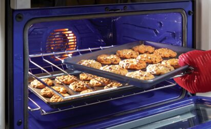 A tray of cookies is being taken from the LG Oven, with baking made easy via its LG ProBake Convection ®