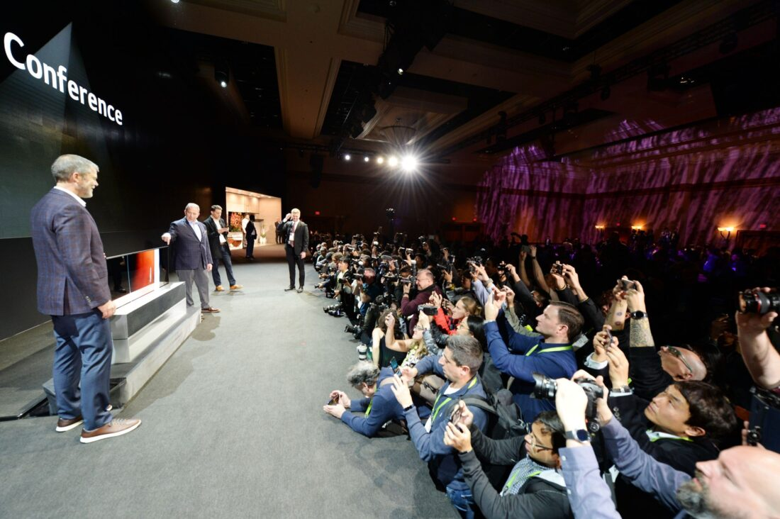 David VanderWall, Senior Vice President of Marketing at LG Electronics USA and Tim Alessi Senior Director of Product Marketing for Home Entertainment Products at LG Electronics USA are onstage discussing the LG SIGNATURE OLED TV R at LG's CES 2019 Press Conference while a number of reporters take pictures of the TV.