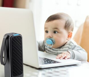An adorable baby stares at a laptop monitor as the LG PuriCare Mini Air Purifier works in the foreground