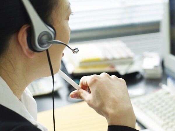 A woman taking a call at her computer while wearing a headset