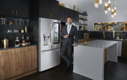 A man in suit standing in front of LG InstaView Door-in-Door™ refrigerator in a kitchen, holding a glass of beverage with Craft Ice™