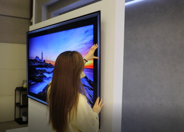 A woman takes a closer look at the thinness of the LG GX Gallery series TV