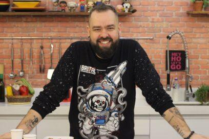 Filipe Nascimento, the star and founder of Micro Sobrevivência, smiles for the camera in his kitchen