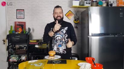 Filipe Nascimento smiles and gives a thumbs up with the burger he just made
