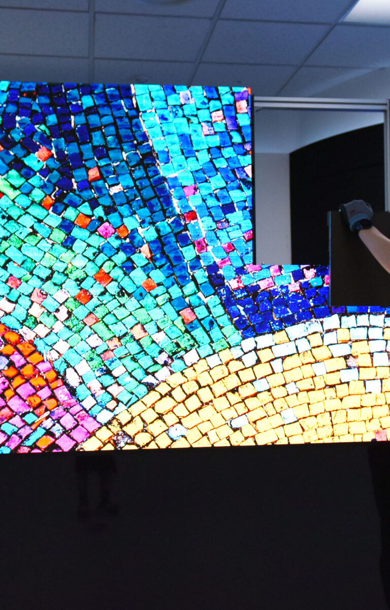 A man demonstrating how easy LG LED SIGNAGE is to install as he fits one of the final LED panels to complete a colorful display
