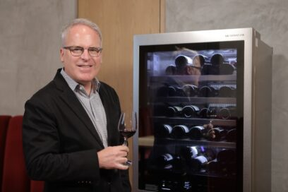 Famous wine critic James Suckling samples a glass of wine next to the new LG SIGNATURE Wine Cellar