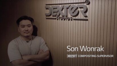 Wonrak Son, head of the composition team at Dexter Studios, is standing beside his company's logo