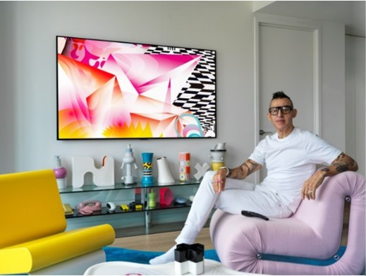 Karim Rashid sits next to the LG GALLERY DESIGN TV which is displaying his painting, DREAMSKAPE