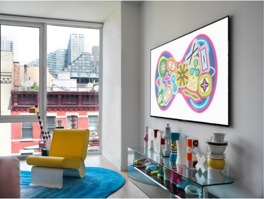 A room with a view is decorated with colorful items and the wall-mounted LG GALLERY DESIGN TV which is displaying Karim Rashid's KOSMOS