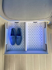 A look at the shoe storage box located below the seats of the IONIQ Concept Cabin, with it open and holding a pair of slippers with room for one more