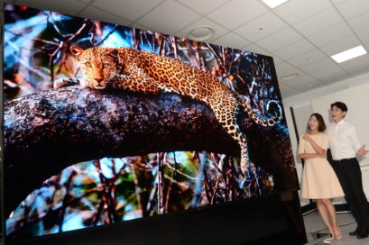A wide image of two people looking at the LG MAGNIT displaying a magnificent leopard in awe, the shot showing just how large the display really is