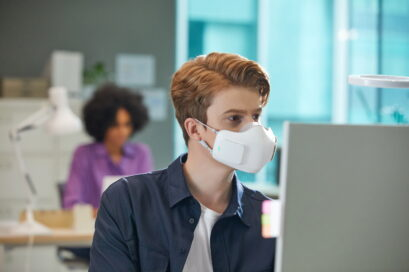 A man in an office wearing LG PuriCare™ wearable Air Purifier