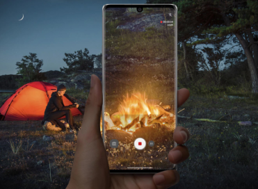 A person using LG VELVET's ASMR recording feature and Voice Bokeh to record a campfire during a trip with friends